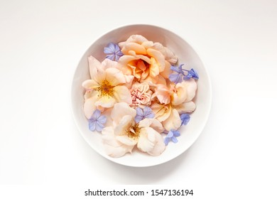 Pastel flowers in a white bowl centered on white background.