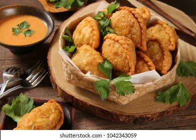 Pastel Goreng. Peranakan snack of fried puff pastry with filling of sautéed vegetable and chicken. Served in woven basket garnished with celery leaves; accompanied with spicy peanut sauce.