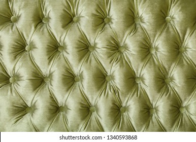 Pastel green velvet capitone textile background, retro Chesterfield style checkered soft tufted fabric furniture diamond pattern decoration with buttons, close up