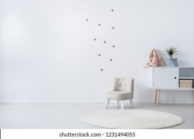 Pastel grey armchair next to wooden cabinet with books, toy and green plant in grey pot, copy space and golder stars stickers on empty white wall