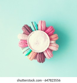 Pastel macarons around a coffee cup