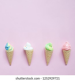 Pastel meringue on ice cream cones on pink background