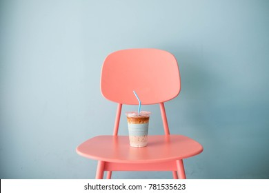Pastel and minimal concept : A clear plastic cup of ice coffee latte with pastel blue straw on pastel pink table on pastel blue background, close up, copy space