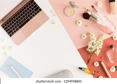Pastel office table desk with air laptop, leaves, spring flowers, clipboard and beauty accessories, top view, flat lay. Home fashion women office workspace isolated on white pink coral background.