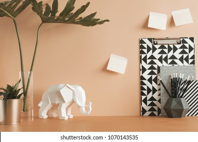 Pastel orange desk with leafs, elephant, plant, office accessories and sticky notes. Artist workspace.