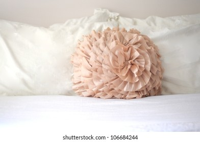 Pastel peach decorative pillow on white sheets in bedroom