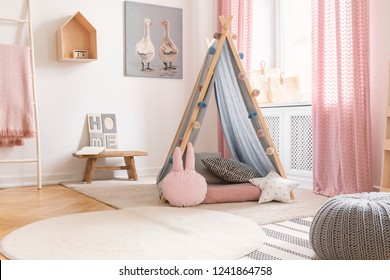 Pastel pillows in front of tent in girl's bedroom interior with pink drapes and poster. Real photo