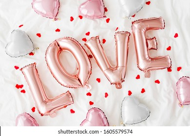 """Pastel pink Air Balloons in the shape of the word """"Love"""" with hearts on bed. Love concept. Holiday, celebration. Valentine's Day or wedding/bachelorette party decoration. Foil balloon"""