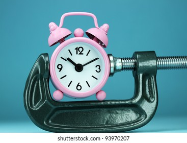 A pastel pink alarm clock placed in a Grey clamp against a pastel purple background, asking the question do you manage your time effectively.