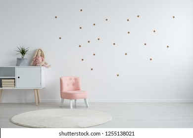 Pastel pink armchair next to wooden cabinet with books, toy and green plant in grey material pot, copy space and golder stars stickers on empty white wall, round carpet on the floor
