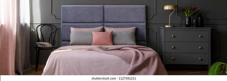 Pastel pink bedclothes on king-size bed with soft bedhead standing in dark bedroom interior with gold lamp and fresh tulips on grey cupboard