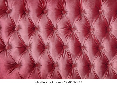 Pastel pink capitone textile background, retro Chesterfield style checkered soft tufted fabric furniture decoration with buttons, close up