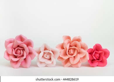 Pastel pink color set of four roses.  All flowers are handmade by sugar fondant and all are edible - isolated with white background - front view