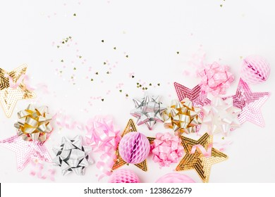 Pastel Pink confetti, bows and paper decorations. Flat lay, top view. Holiday composition for birthday party, New year/Christmas celebration or hen party  concept theme. Flat lay, top view