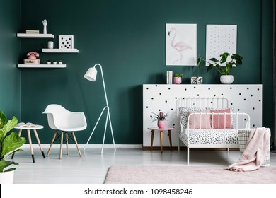 Pastel pink decorations in a scandi bedroom interior for a teenage girl with modern, white furniture and dark green walls