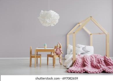 Pastel pink girl's bedroom with a modern, wooden bed, small table, and a stuffed animal sitting by it
