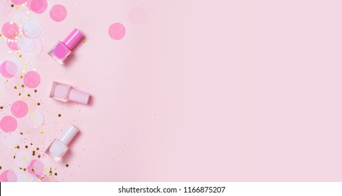 Pastel pink nail polishes and confetti, stars and sparkles. Bright and festive background. Manicure concept. Top view, flat lay. copyspace for your text.