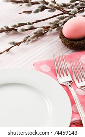 A pastel pink place setting is decorated for an Easter meal leaving ample copy space over a white plate.