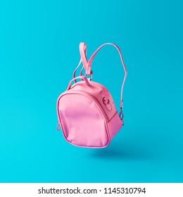 Pastel pink school bag floating on sky blue background. Surreal modern still life. Back to school minimal concept.