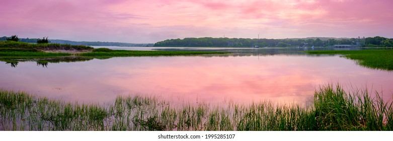 Pastel Pink Sunset on Cape Cod. Peaceful Seascape over Falmouth Marsh Bay with Clouds Reflected on Sea Water. Panoramic Horizontal Coastal Landscape with Space for Text or Design.