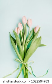 Pastel pink tulip flowers bouquet on pale blue background. Flat lay, top view. Minimal spring floral concept.