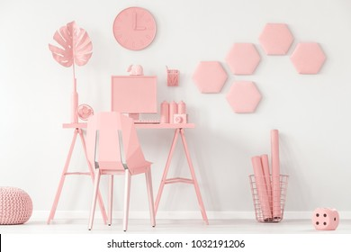 Pastel pink and white home office interior with decorative honeycomb on the wall and computer on the desk