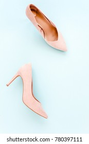 Pastel pink women high heel shoes on blue background. Flat lay, top view trendy fashion feminine background. Beauty blog concept. Fashion blog look.