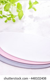 Pastel plates on white shine table on a fresh mint background. Tableware set. Dishes for a meal. Empty template to put your food on the plate. picnic