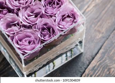Pastel purple hue roses in clear acrylic crystal flower box. Square glass gift box. On wooden table from above