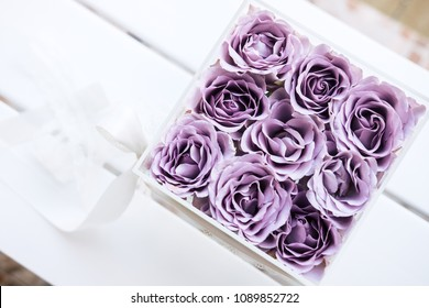 Pastel purple hued roses in clear acrylic crystal flower box. Square glass gift box. On white wooden table from above, copyspace