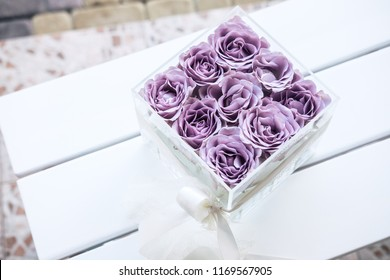 Pastel purple hued roses in clear acrylic crystal flower box. Square glass gift box. On white wooden table from above