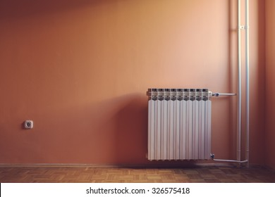 Pastel retro color of warm windows natural illuminated empty room with water central heating radiator and power outlet.