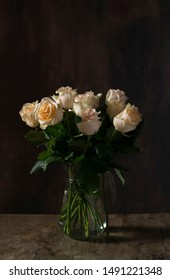 Pastel roses in a vase on a dark background