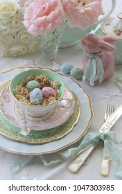 Pastel speckled eggs in a nest in a vintage  tea cup with pink bunny rabbit, spring roses, silver cutlery flatware - Easter high tea party wedding