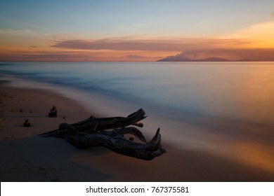 Pastel sunset colors produced by an volcanic ash cloud from Montserrat, seen from Antigua. Some driftwood in the foreground.