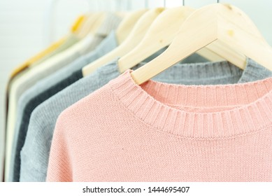 Pastel sweater knitted clothing hanging on rack collection in trendy sale retail store.