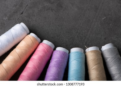 Pastel threads on grey background with selective focus