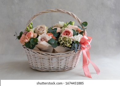 Pastel trend colored flowers in white basket isolated, floristic wedding present background, March 8, Womens, Mothers day postcard concept