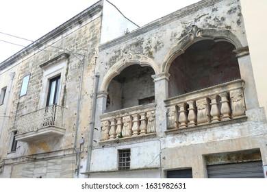 Pastel walls on narrow street with ornate doors and balconies, Nardo, Puglia, Italy