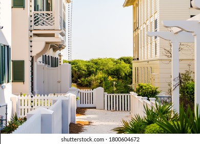 Pastel white yellow new urbanism architecture exterior of houses buildings in Florida beach home condo with rain chains hanging