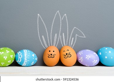 Pastel-colored Easter eggs and creative bunnies on the white table, close-up. Grey background. Funny Easter eggs.