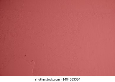 Pastel-red concrete wall with plastered structures. Red background in industrial design. Textured stone wall as texture and creative element for art and collagen.