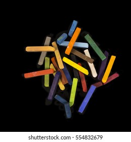Pastels chalk sticks of many colors piled on a black background.