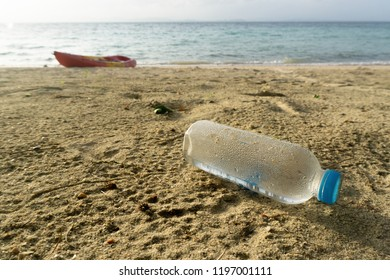 Pastic bottle on sand beach in sunset time