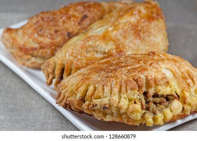 pasties filled with minced meat on a white plate with beige background
