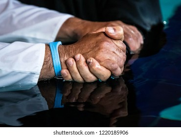 pastor holding someone's hands before baptism