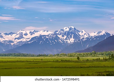 pastoral panorama of the chugach mountains and forest southeast of anchorage alaska with green meadows in the foreground