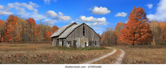A pastoral scene, Old barn and dirt road surrounded by the colors of autumn , Michigan, Lower Peninsula, USA