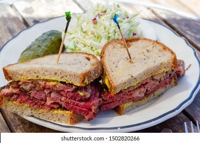 Pastrami sandwich sliced in half on rye bread with mustard on a white plate on a wood table as seen from above. Coleslaw and dill pickle on side. Toothpicks in both halves of sandwich.