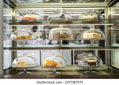 Pastries and cakes on showcase in the pastry shop. Glass lid